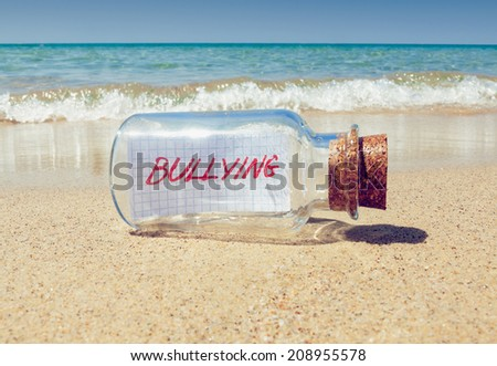 """Creative bullying concept. Bottle with a message """"bullying"""" on beach  - stock photo"""