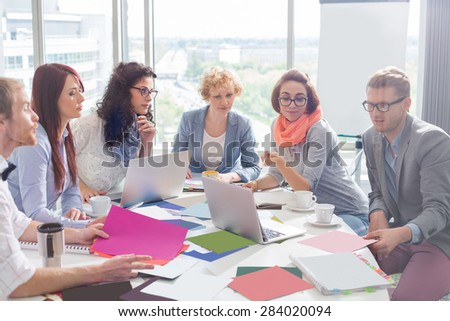 Creative business colleagues analyzing photographs at conference table in office - stock photo