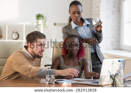 Creative business colleagues discussing over computer in office - stock photo