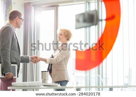 Creative business colleagues shaking hands in office - stock photo
