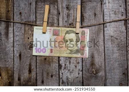 Creative business finance making money concept. Money on a clothespin on a wooden background. Ukrainian hrivna - stock photo