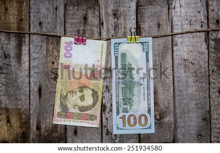 Creative business finance making money concept. Money on a clothespin on a wooden background . US dollars, hrivna ukrainian - stock photo