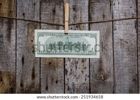 Creative business finance making money concept. Money on a clothespin on a wooden background. US dollar - stock photo