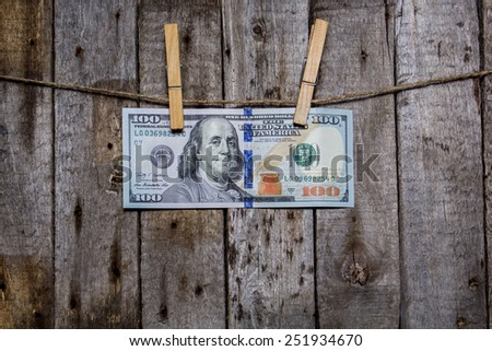 Creative business finance making money concept. Money on a clothespin on a wooden background. US dollars - stock photo
