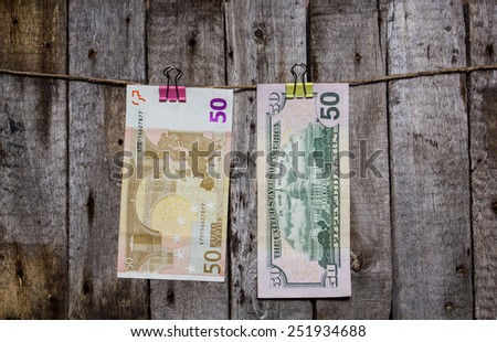 Creative business finance making money concept. Money on a clothespin on a wooden background . US dollars, euros - stock photo
