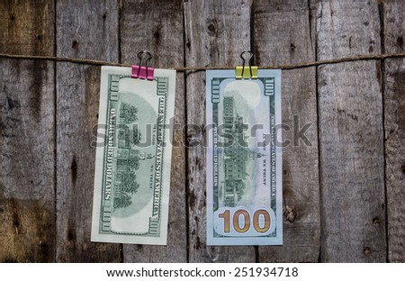 Creative business finance making money concept. Money on a clothespin on a wooden background. US dollars new and old - stock photo
