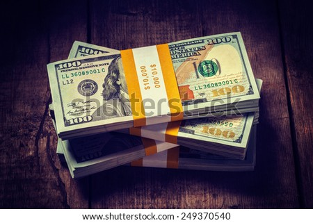 Creative business finance making money concept - Vintage retro effect filtered hipster style image of stacks of new 100 US dollars 2013 edition banknotes (bills) bundles isolated on wooden background - stock photo