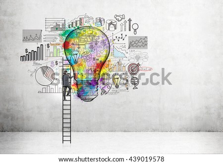 Creative business idea concept with businessman on ladder drawing colorful light bulb sketch and business charts in concrete room - stock photo
