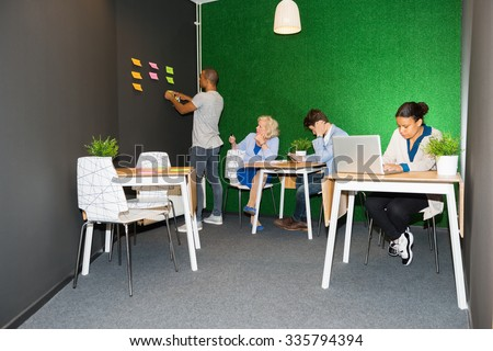 Creative business people working in modern office lobby - stock photo