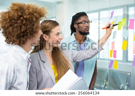 Creative business team pointing at adhesive notes in office - stock photo
