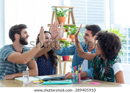 Creative business team putting their hands together in meeting at office - stock photo