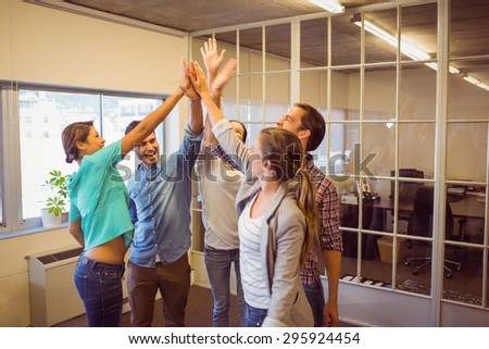 Creative business team raising their hands at the office - stock photo