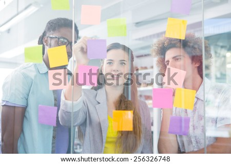 Creative business team writing on adhesive notes in office - stock photo