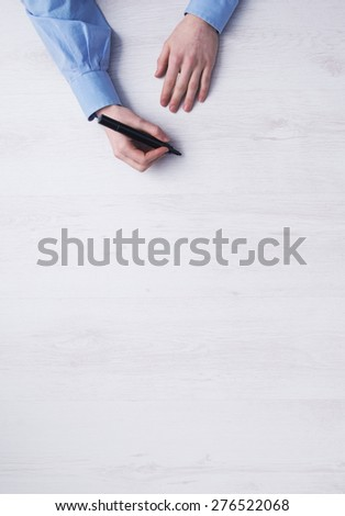 Creative businessman working at office desk and sketching with a black marker, hands detail top view - stock photo