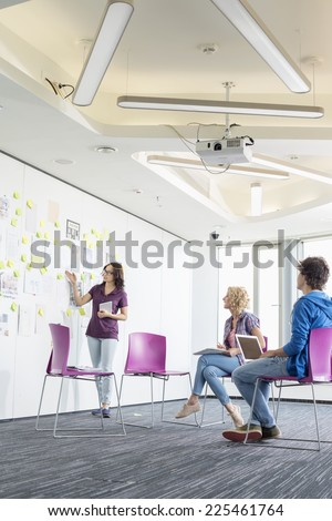 Creative businesswoman giving presentation to colleagues in office - stock photo