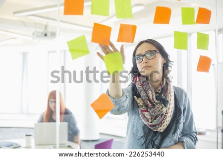 Creative businesswoman reading sticky notes on glass wall with colleague working in background at office - stock photo