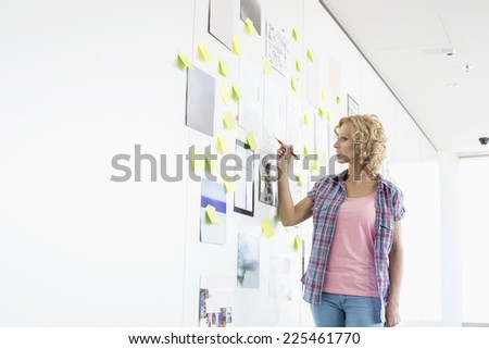 Creative businesswoman writing on sticky paper in office - stock photo