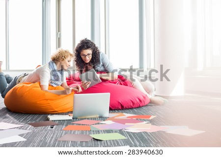 Creative businesswomen using tablet PC while relaxing on beanbag chairs at office - stock photo