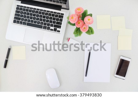 Creative Chaos. A high angle view of laptop, blank paper and lots of sticky notes around - stock photo