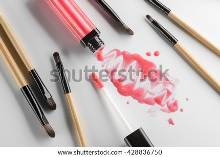 Creative chaos in the process of putting on the make-up. Spilled out lipstick of its tube with glossy microelements for shiny lips. Scattered brushes and an applicator. - stock photo