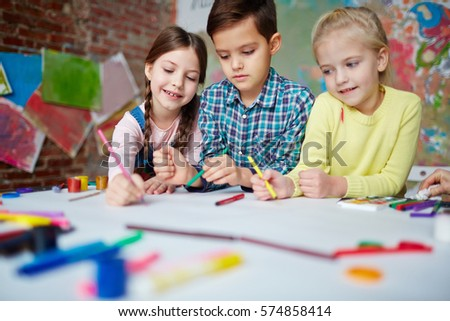 Creative children drawing with crayons in elementary school or kindergarten