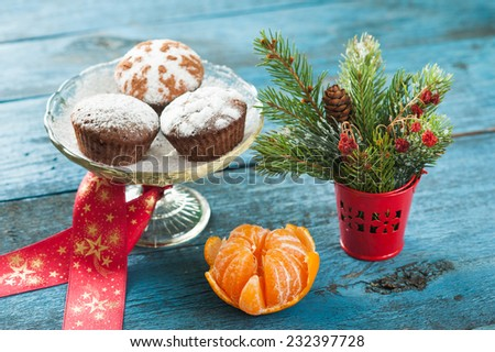 Creative Christmas and New Year decoration with cakes, red ribbon, peeled tangerine, spruce tree branches and red berries in a decorative bucket placed on aged blue wooden surface - stock photo