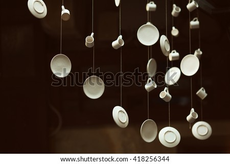 Creative coffee shop and cafe with avant-garde style decoration. Hanging porcelain cups and saucers, old wooden doors on wall. Arty vintage style. Indoor shot - stock photo
