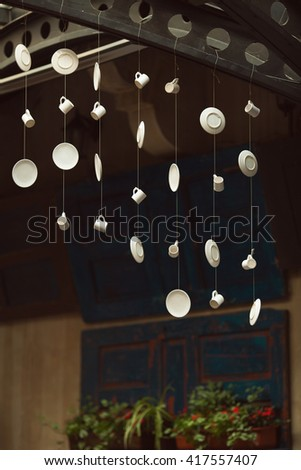 Creative coffee shop and cafe with avant-garde style decoration. Porcelain cups and saucers hang on metal bar, old wooden doors on wall. Arty vintage style. Indoor shot