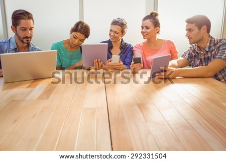 Creative colleagues with laptop and digital tablet in the office - stock photo