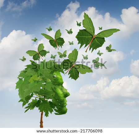 Creative communication and intelligent marketing concept as a tree shaped as a human head with flying leaves as leaf butterflies spreading the message and sharing innovative thoughts and imagination. - stock photo