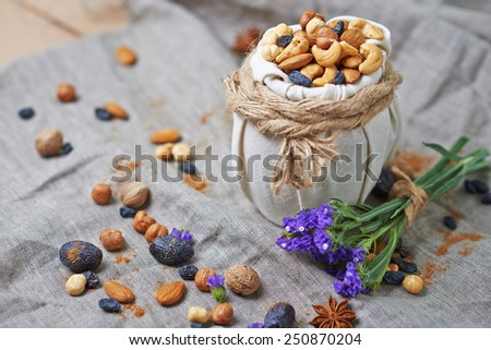 creative composition a mix of different nuts in a decorative pot on a tablecloth - stock photo