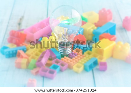 Creative concept light bulb and colorful block toy on white wooden floor - stock photo