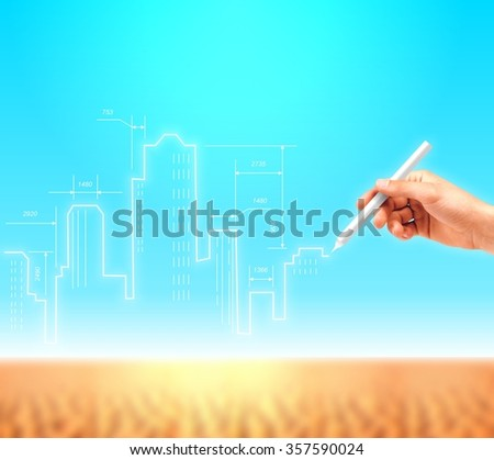 Creative concept of construction of modern buildings in the desert areas. Hand draws an architectural plan of the skyscrapers against the blue sky. - stock photo