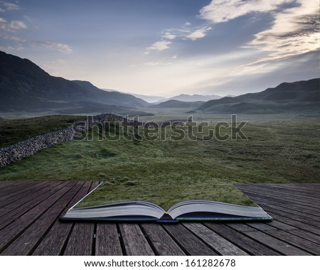 Creative concept pages of book View along countryside fields towards misty Snowdonia mountain range in distance - stock photo