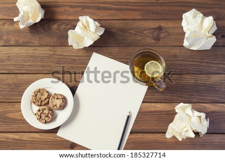Creative concept. Pencil on a white paper with crumpled paper ball, a white plate with chocolate cookies and a cup of tea.. All on a wooden table. - stock photo