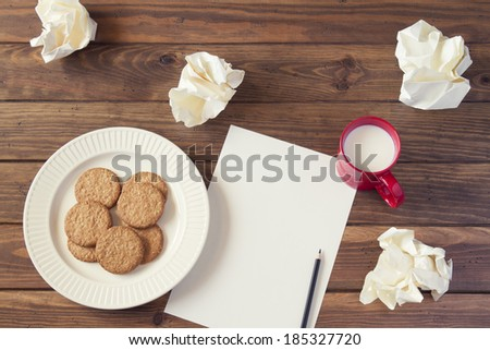 Creative concept. Pencil on a white paper with crumpled paper ball, a white plate with cookies and a red mug of milk. All on a wooden table. - stock photo