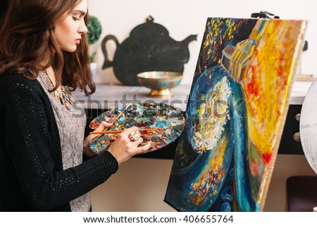 Creative contemporary painter paints a colorful abstract painting. Closeup of painting process in art workshop. Creative positive woman painter paints in her studio colorful abstract painting  - stock photo