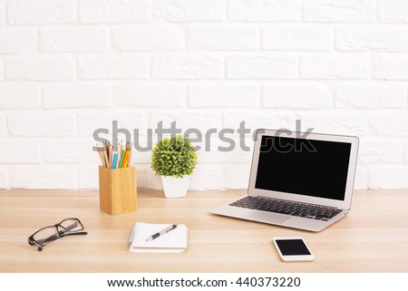 Creative designer desktop with blank laptop, smart phone, glasses, stationery and decorative items on white brick background. Mock up - stock photo