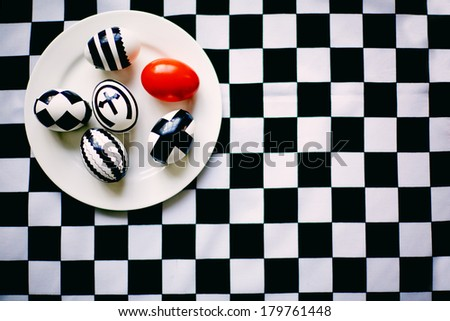 Creative Easter eggs on plate against chess background - stock photo