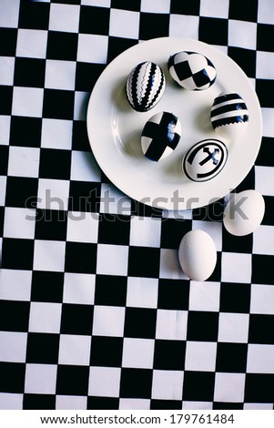 Creative Easter eggs on plate with two white eggs near by against chess background