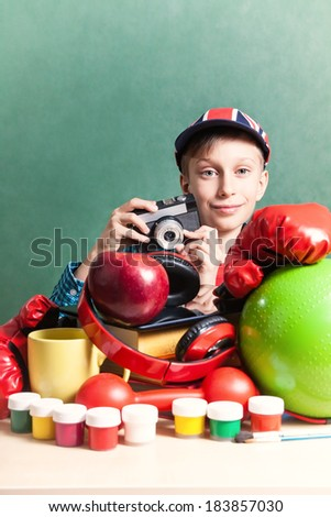 Creative education concept. Funny schoolboy sitting at table with colorful school accessories holding a vintage camera smiling  - stock photo