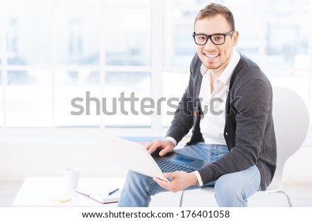 Creative executive. Handsome young man in glasses working on computer and smiling at camera while sitting at his working place - stock photo