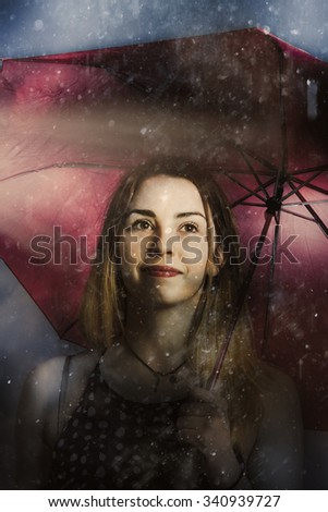 Creative fine art of a beautiful woman walking unhindered through the pouring rain with umbrella. Resilient in storms by positive thinking