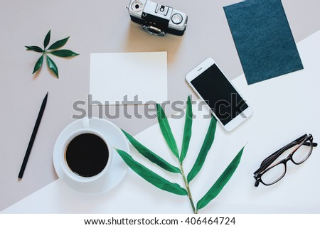 Creative flat lay photo of workspace desk with smartphone, coffee, film camera, blank paper and envelope with copy space background, minimal style - stock photo