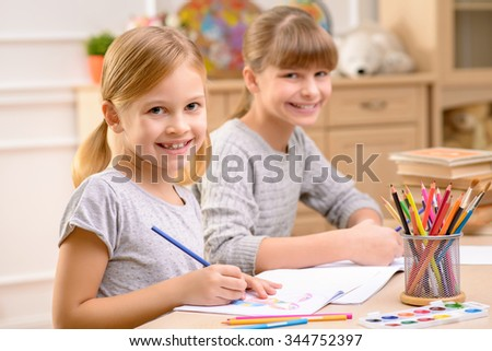 Creative girls. Pleasant smiling little sisters sitting at the table and feeling content while drawing