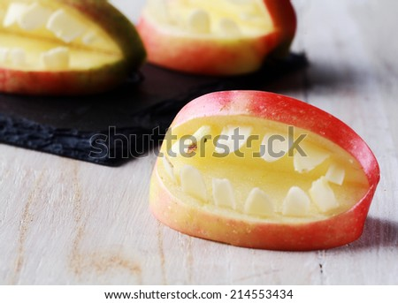 Creative Halloween apple with teeth in a cutout shape with an open mouth for a healthy scary trick-or-treat favor - stock photo