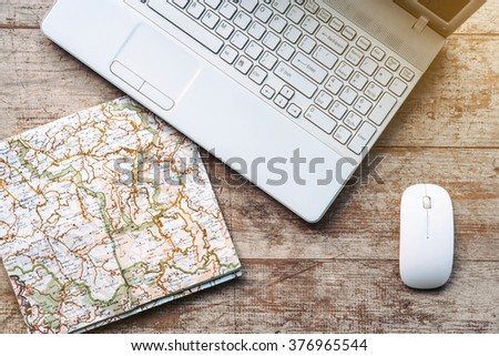 Creative horizontal top view photo of business objects on light colored woodblocks. There are laptop, map and optical mouse - stock photo