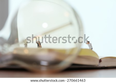 Creative idea concept - miniature photographer with vintage light bulb on open paper notebook