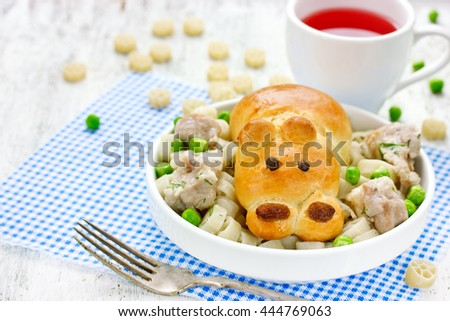 Creative idea for a children's meal - bread in the form of animal hippo, meat stewed in a sauce, green peas and garnish selective focus