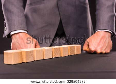 Creative idea. Young businessman presenting creative idea using wood cubes. Studio shooting isolated on Black background